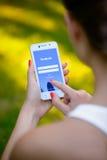 ZAPORIZHZHYA, UKRAINE - 20. SEPTEMBER 2014: Junge Frau, die Anwendung Facebook-Sozialen Netzes an ihrem intelligenten Telefon ver Stockbild
