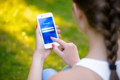 ZAPORIZHZHYA, UKRAINE - 20. SEPTEMBER 2014: Junge Frau, die Anwendung Facebook-Sozialen Netzes an ihrem intelligenten Telefon ver Stockfotos