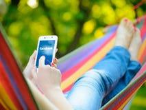 ZAPORIZHZHYA, UKRAINE - 20. SEPTEMBER 2014: Junge Frau, die Facebook-Anwendung an ihrem intelligenten Telefon verwendet Stockbilder
