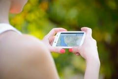 ZAPORIZHZHYA, UKRAINE - 20. SEPTEMBER 2014: Junge Frau, die Google Maps an ihrem intelligenten Telefon verwendet Lizenzfreies Stockfoto