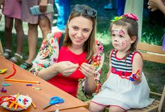 Mother and daughter participating at art and craft outdoor workshop. Zaporozhia/Ukraine- June 2, 2018: Charity Family festival – mother and stock images