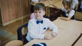 Zaporozhye, Ucrânia - 1º de setembro de 2018: retrato de um primeiro graduador em uma camisa branca e em um laço azul que sentam- imagens de stock royalty free
