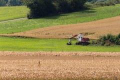 Zappatore con la capanna e terra su un paesaggio rurale del campo di grano Fotografie Stock