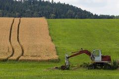 Zappatore con la capanna e terra su un paesaggio rurale del campo di grano Immagini Stock