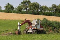Zappatore con la capanna e terra su un paesaggio rurale del campo di grano Fotografie Stock Libere da Diritti