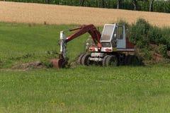 Zappatore con la capanna e terra su un paesaggio rurale del campo di grano Immagine Stock Libera da Diritti