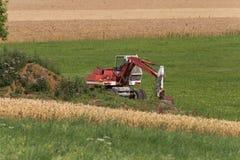 Zappatore con la capanna e terra su un paesaggio rurale del campo di grano Fotografia Stock
