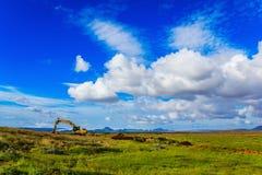 Zappatore nel campo sotto cielo blu Immagini Stock