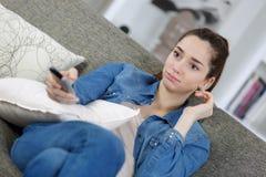 Zapping tv för ung flicka från den borrade soffan Royaltyfri Bild