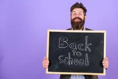 Zaprasza świętować dzień wiedza Nauczyciela brodaty mężczyzna stoi blackboard z inskrypcją z powrotem i trzyma szkoła fotografia royalty free