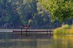 Zapraszająca Parkowa ławka na molu Nad Nieociosanym jeziorem Zdjęcie Royalty Free