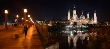 Zaragoza at night. Passerby are having a night walk in the Stone bridge (Puente de Piedra) across the river Ebro in Zaragoza. The spotlit cathedral (Basilica of Stock Image