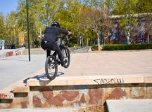Zaragoza , Spain; 03 23 2019 : sport man wearing helmet, t-shirt, gloves and trousers in black riding a bmx bicycle getting up the royalty free stock photo