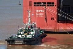 Zarate, Argentina - 22 de agosto de 2018: Navio grande do portador de carro que deixa o porto de Zarate com o auxílio do barco do fotos de stock