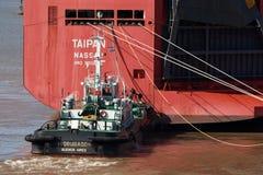 Zarate, Argentina - 22 de agosto de 2018: Navio grande do portador de carro que deixa o porto de Zarate com o auxílio do barco do imagens de stock