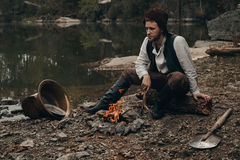 Zarośnięty poszukiwacza złota warmin w górę pobliskiego ogienia na skalistym banku Fotografia Stock