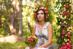 Zarte Frau im Kranz von rosafarbenen Blumen Lizenzfreie Stockbilder