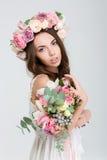 Zarte reizend Braut im Rosenkranz mit Blumenstrauß von Blumen Lizenzfreie Stockfotos