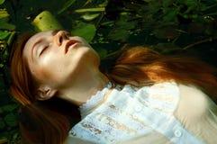 Zarte Schwimmen der jungen Frau im Teich unter Seerosen lizenzfreie stockfotografie