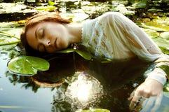 Zarte Schwimmen der jungen Frau im Teich unter Seerosen stockfotos