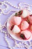 Zarter Erdbeersatz auf der weißen Platte glasiert in der rosa und weißen Schokolade verziert mit Streifen und Perlenhalskette auf lizenzfreie stockfotos