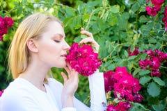 Zarter Geruch und Naturschönheit Mädchen und Blumen auf Naturhintergrund Rosen-Auszugöl-Aromaprodukt frech stockfoto