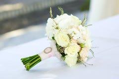 Zarter schöner Brautblumenstrauß der Braut liegt auf dem Tisch stockbild