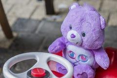 Zartes Bild eines purpurroten Teddybären, der auf einem roten Auto für Kinder sitzt stockbild