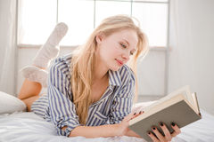 Zartes blondes weibliches Lügen auf Bett- und Lesebuch Stockfotos