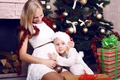 Zartes Foto des kleinen Mädchens mit ihrer schwangeren Mutter neben einem Weihnachtsbaum Lizenzfreie Stockbilder