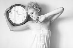 Zartes junges Mädchen mit dem gelockten Haar und einer großen Uhr in seinen Händen Stockfotos