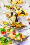 Zartheit, Imbisse und Frucht auf der festlichen Tabelle im Restaurant feier lebesmittelanschaffung Tartlets, Salate und Fruchtkor stockfoto