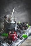 Zarzamora, jugo de la zarzamora y atasco maduros en una tabla de madera Fondo oscuro foto de archivo libre de regalías