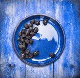 Zarzamoras en cuenco en el fondo de madera azul, visión superior foto de archivo libre de regalías