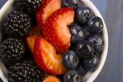 Zarzamoras, fresas, arándanos en un cuenco blanco Imagen de archivo libre de regalías