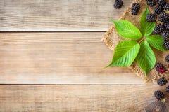 Zarzamoras frescas con las hojas en fondo de madera en estilo rústico Foto de archivo libre de regalías