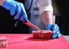 Zarzyna tnącego wieprzowiny mięso, szef kuchni ciie świeżego surowego mięso, szefa kuchni kulinarny jedzenie w kuchni zdjęcie royalty free
