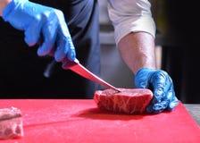 Zarzyna tnącego wieprzowiny mięso, szef kuchni ciie świeżego surowego mięso, szefa kuchni kulinarny jedzenie w kuchni zdjęcia royalty free