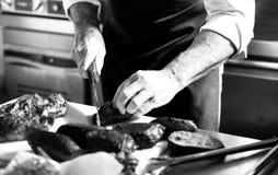 Zarzyna tnącego wieprzowiny mięso, szef kuchni ciie świeżego surowego mięso, szefa kuchni kulinarny jedzenie w kuchni fotografia stock