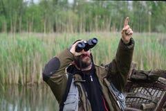 Zasavica Serbien - April, 19th 2014 : Man med att hålla ögonen på för kikarefågel peka upp fingret Arkivfoton