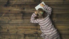 Zasięrzutna dziecko dziewczyna pisze Santa Claus prezenta liście na rocznika drewnianym tle Teksta lub logo kopii przestrzeń Vert zbiory wideo