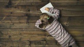 Zasięrzutna dziecko dziewczyna pisze Santa Claus prezenta liście na rocznika drewnianym tle Teksta lub logo kopii przestrzeń Vert zbiory