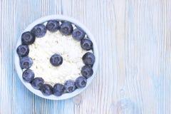 Zasi?rzutna fotografia ?wie?y naturalny cha?upa ser z czarnymi jagodami w ceramicznym pucharze na drewnianym stole Organicznie ec obrazy stock