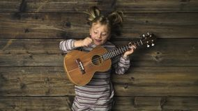 Zasięrzutna szczęśliwa dziecko dziewczyna na rocznika drewnianym tle bawić się ukulele gitarę Teksta lub logo kopii przestrzeń Pi zbiory