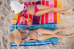 Zasięrzutny widok dwa młodej kobiety garbnikuje w słońcu na plaży Obrazy Stock