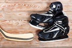 Zasięrzutny widok hokejowy kij i lodowe łyżwy na starym nieociosanym woode Zdjęcia Royalty Free