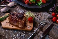 Zasięrzutny widok kolorowi warzywa, cząberów kumberlandy i sól, słuzyć z piec na grillu stkiem na nieociosanym drewnianym kontuar Obrazy Royalty Free