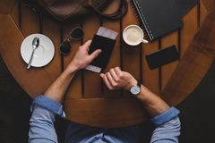 zasięrzutny widok mężczyzna z paszportowego i lotniczego bileta obsiadaniem przy drewnianym stołem z kawą Zdjęcia Stock