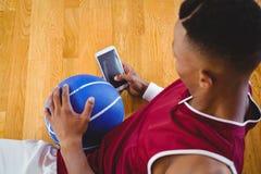Zasięrzutny widok męski gracz koszykówki używa telefon komórkowego Zdjęcia Royalty Free