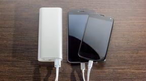 Zasila banka ładuje dwa smartphones - ciemny drewniany tło Zdjęcia Stock